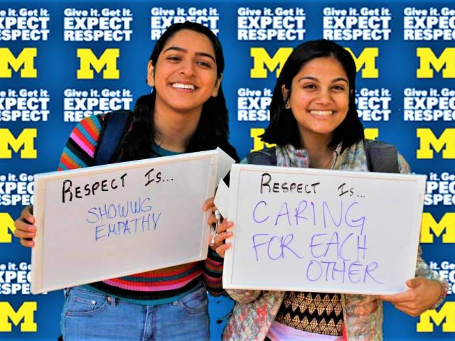 Two students holding up whiteboards saying what respect means to them