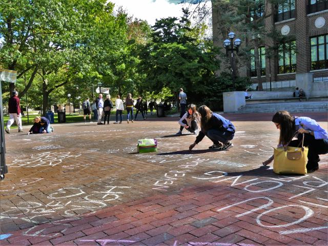 Students chalking positive messages on the Diag